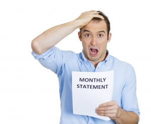 Surprised male holding monthly statement