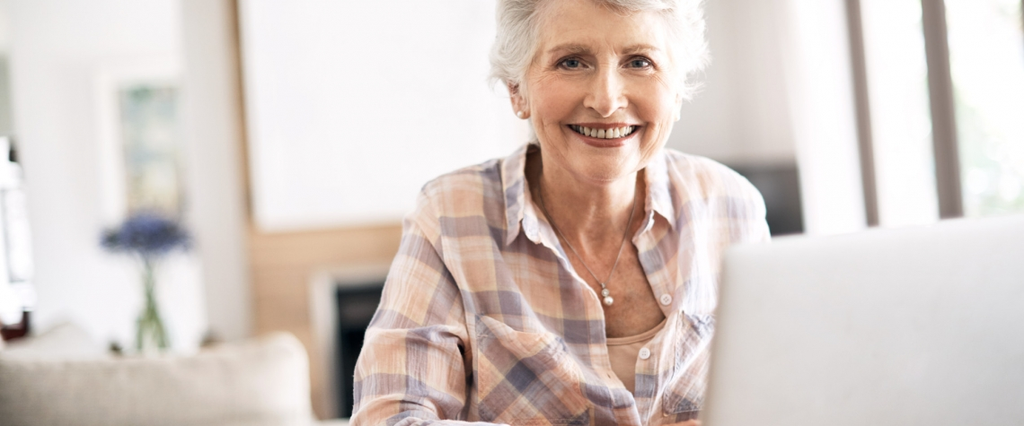 A retired woman checks her eStatements from her home computer