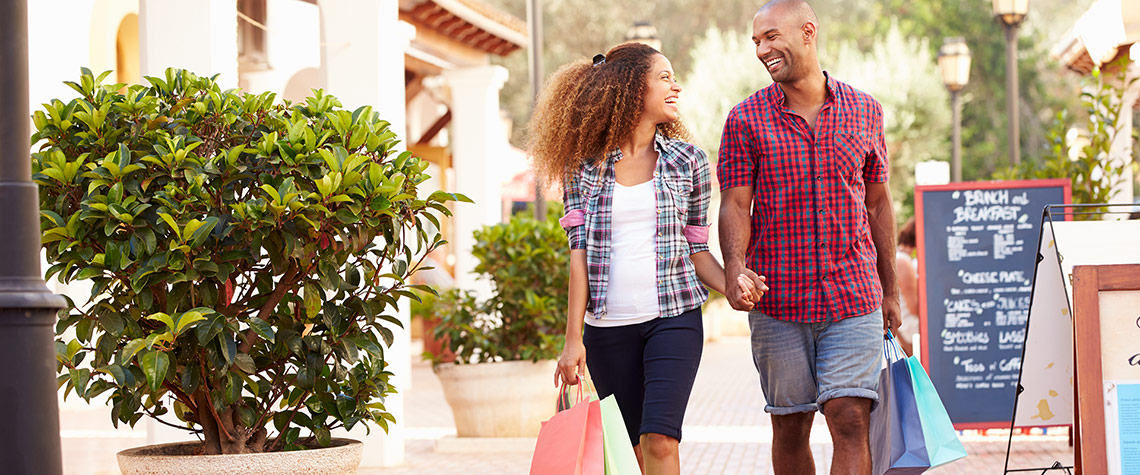 Man and woman holding hands while walking and shopping together