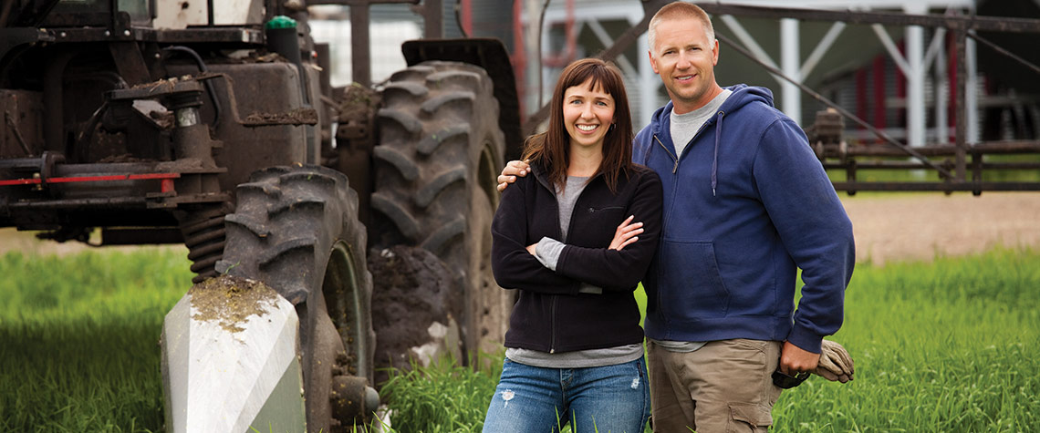 Two Ephrata National Bank agricultural banking customers standing in front of their tractor