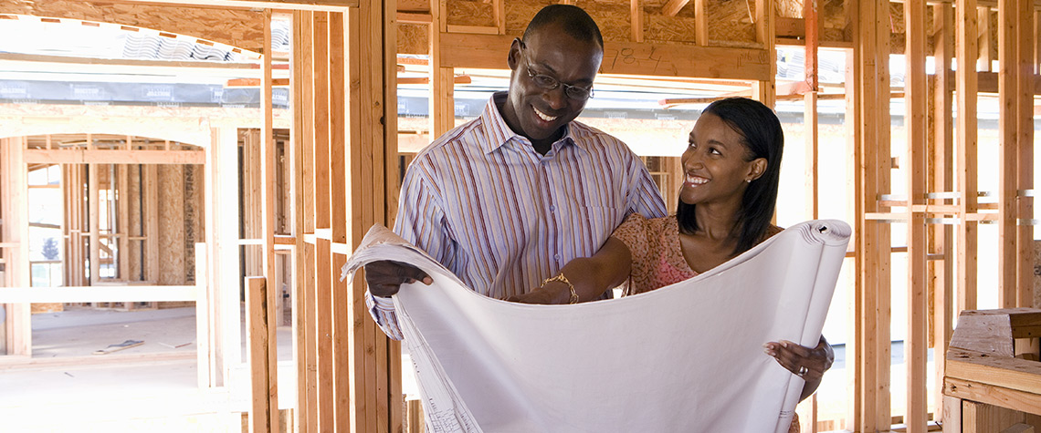 A male and female couple looking at blueprints in a home that is being built