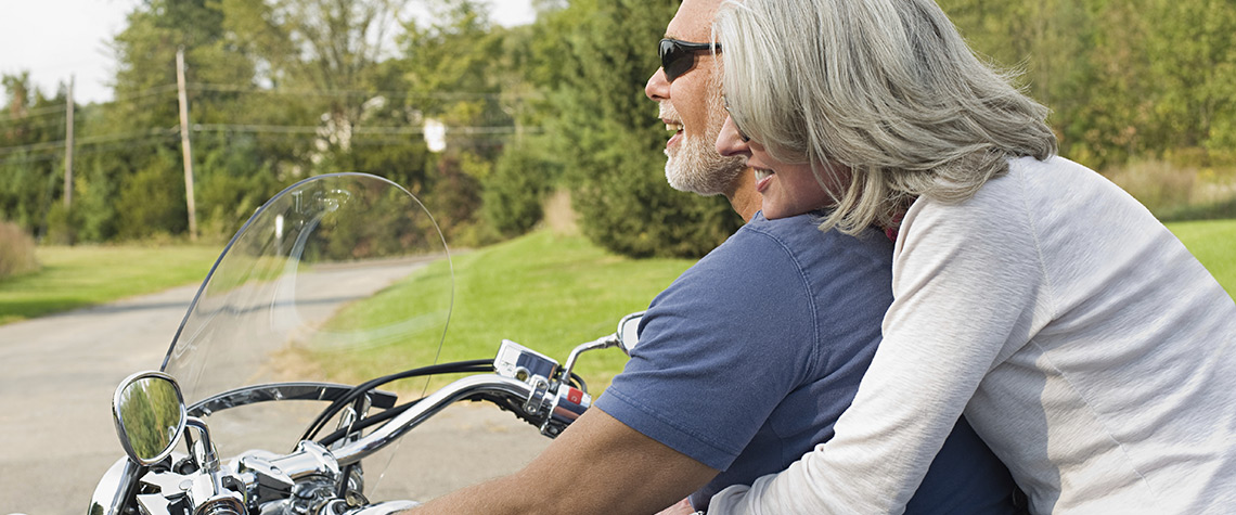 A man and woman riding a motorcycle outdoors
