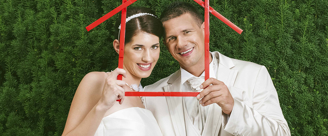 A newly married male and female couple holding the outline of a home