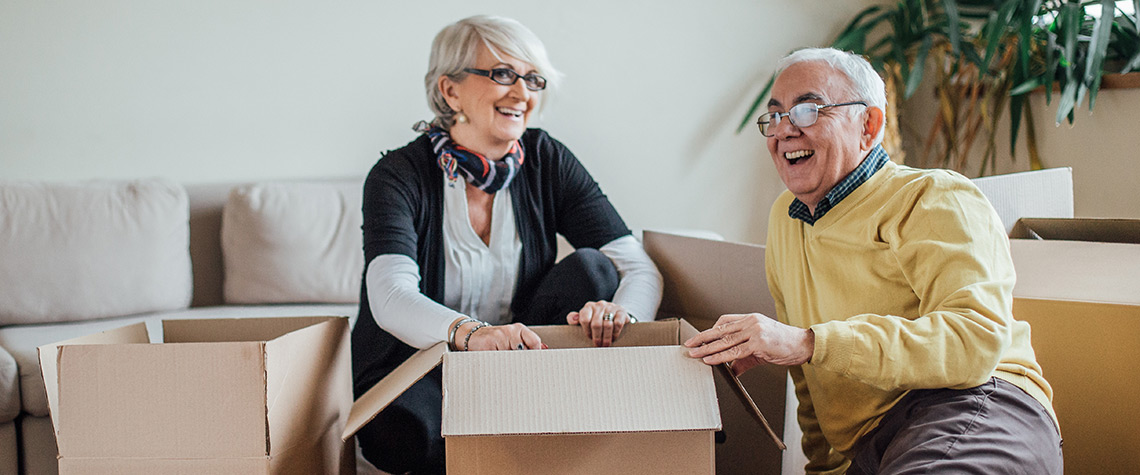 A man and woman unpacking moving boxes in a room