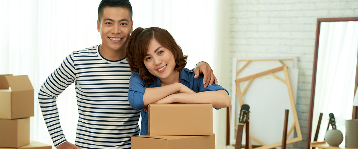 A male and female couple in a room with moving boxes