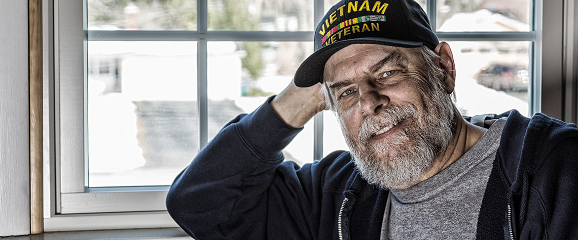 A veteran standing in front of a window