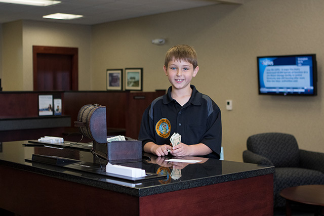 A boy holding money in front of a small treasure chest at the bank