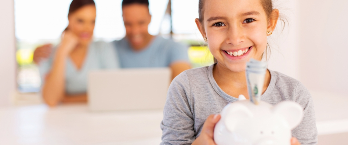 cheerful little girl holding piggybank with parents on background