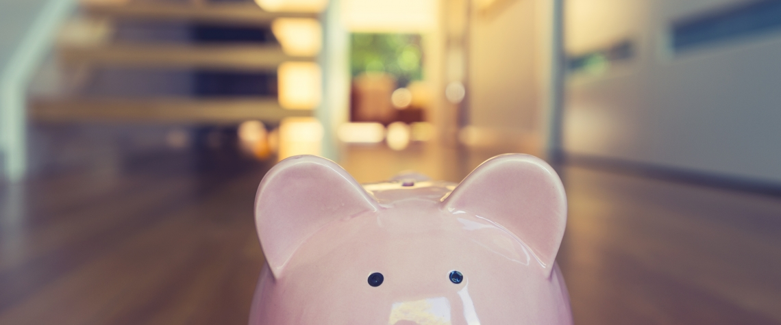 Saving for a home concept. Piggy bank standing at front door with house interior in the background. Pig is pink in foreground and house is modern style. Copy space.