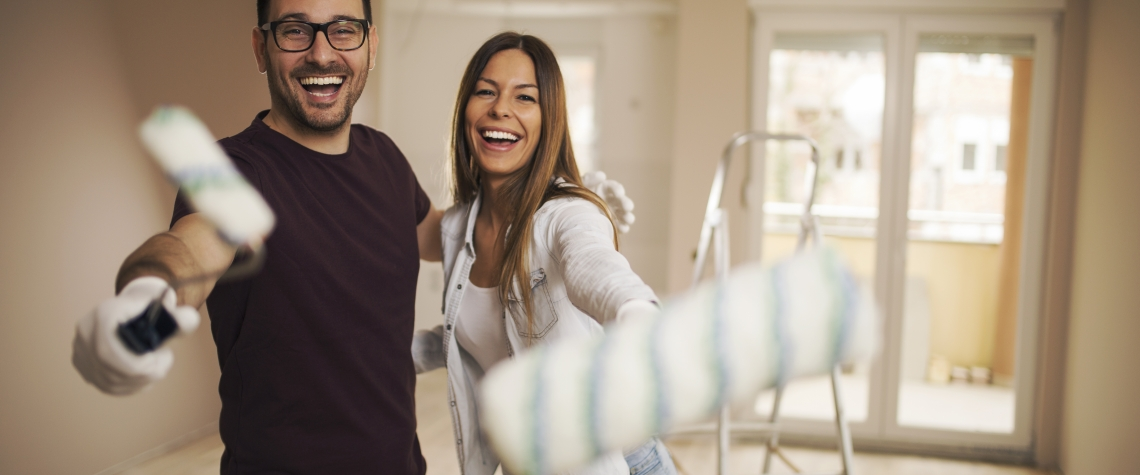 Smiling young couple in their apartment holding painting roller in their hands and laughing.