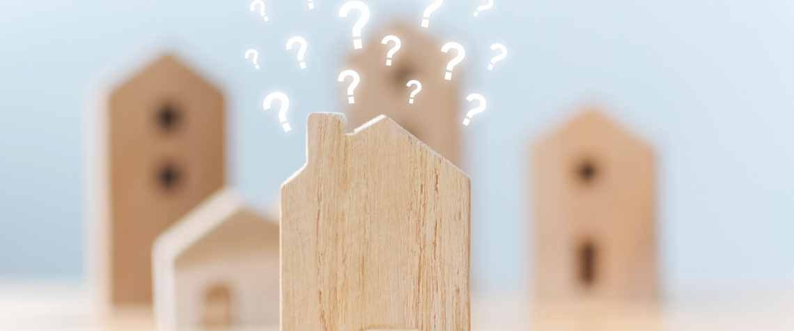 Selective focus wooden houses with question mark on table