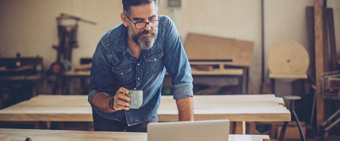 Man with coffee looking at laptop