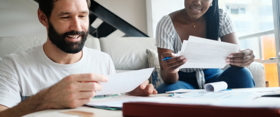 Multiethnic couple filing tax return. African American woman and Caucasian man checking utility bills and banking account. Front View.