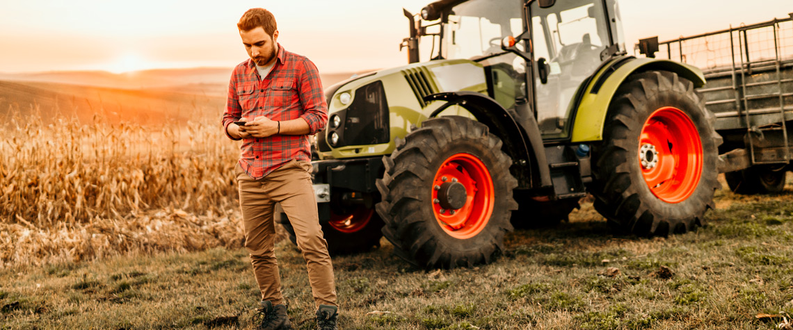 Farmer working on field using smartphone in modern agriculture - tractor background