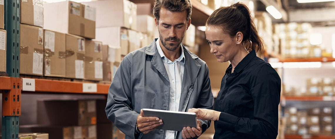 People in warehouse looking at tablet